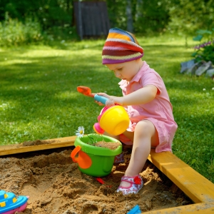 little girl playing in sandbox